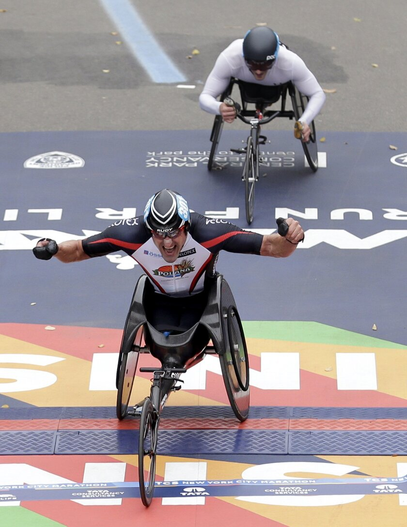 Ernst van Dyk, of South Africa, crosses the finish line first in the men's wheelchair division, just in front of Josh George of the United States, at the 2015 New York City Marathon in New York, Sunday, Nov. 1, 2015. (AP Photo/Seth Wenig)
