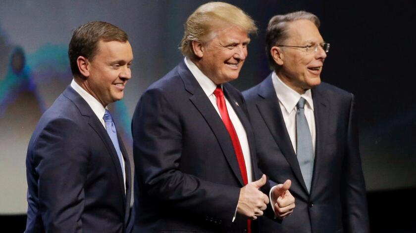 Chris W. Cox (i) presenta a Donald Trump durante una conferencia de la Asociación Nacional del Rifle (NRA). Los acompaña el vicepresidente ejecutivo de la asociación, Wayne LaPierre.