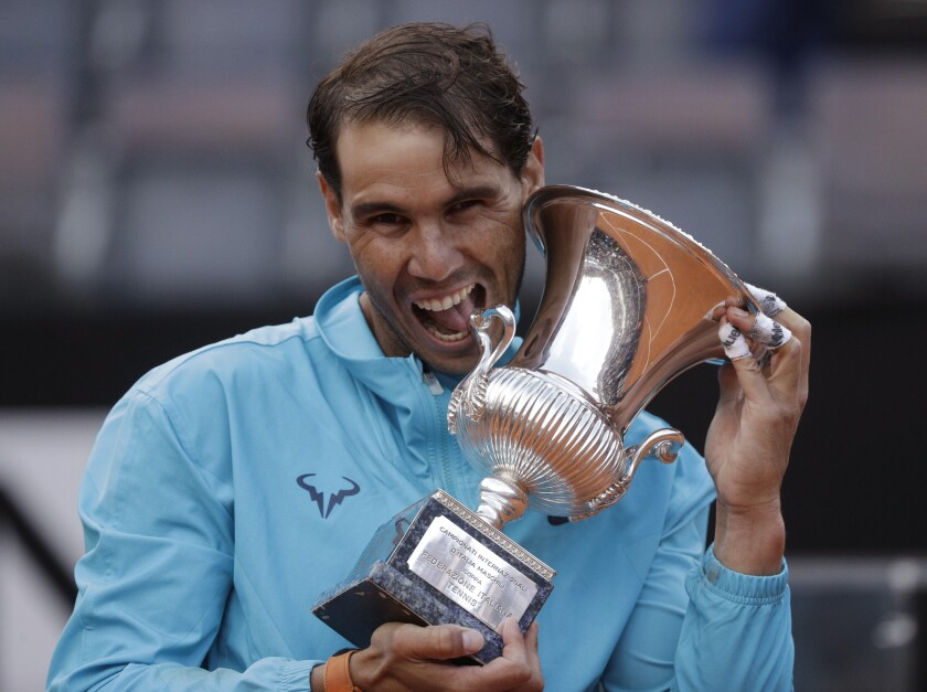 """FILE - In this May 19, 2019 file photo, Rafael Nadal of Spain holds his trophy after winning against Novak Djokovic of Serbia at the end of their final match at the Italian Open tennis tournament, in Rome. Rafael Nadal is preparing his return to tennis after a seven-month layoff at next week's Italian Open. """"The Foro Italico is always a special place for me and even more so this year as it will be my first tournament following a long period without playing,"""" Nadal, who has won the Rome tournament a record nine times, said in a video message played at the event's presentation Tuesday, Sept. 8, 2020. (AP Photo/Gregorio Borgia)"""