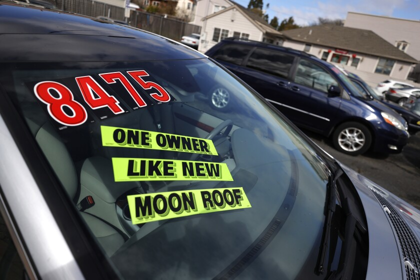 Closeup of a car windshield with stickers that read 'one owner,' 'like new' and 'moon roof.'