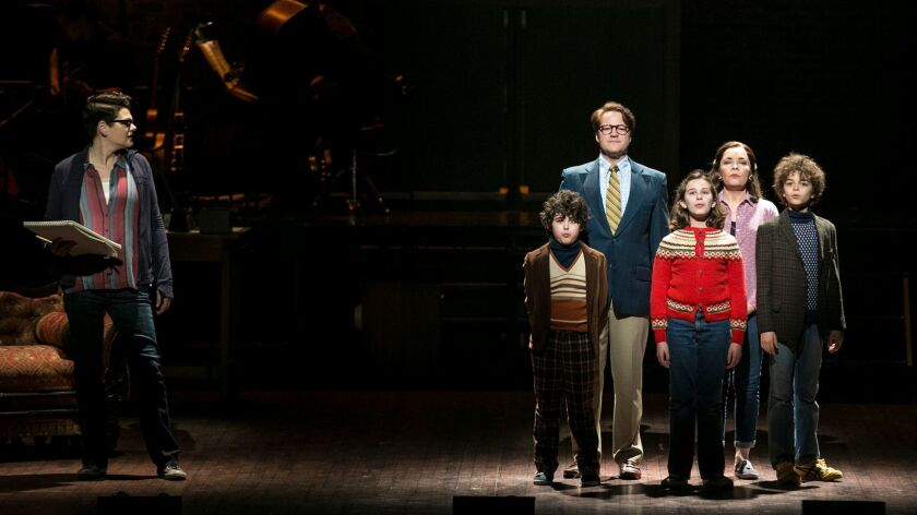 "Alison Bechdel (played by Kate Schindle, left) looks toward her childhood self (Alessandra Baldacchino, in the red sweater) surrounded by her family in ""Fun Home."""