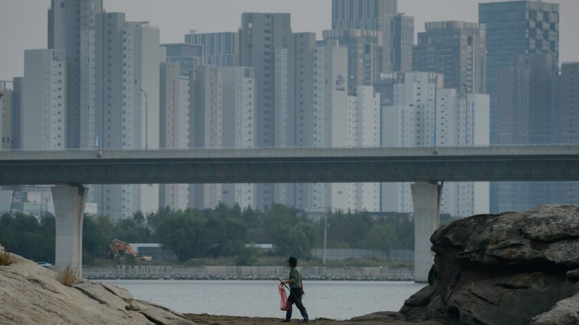 A fisherman walks along the waterfront, dwarfed by the apartment buildings in Songdo
