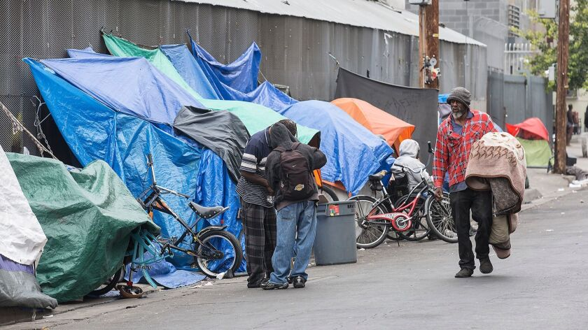 Homeless people gather near tents on L.A.'s Skid Row at San Julian and 6th Streets.