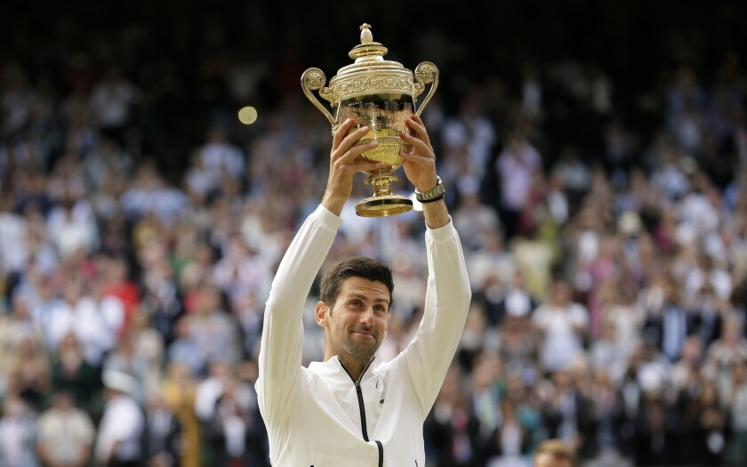 Serbia's Novak Djokovic lifts the trophy after defeating Switzerland's Roger Federer in the men's si