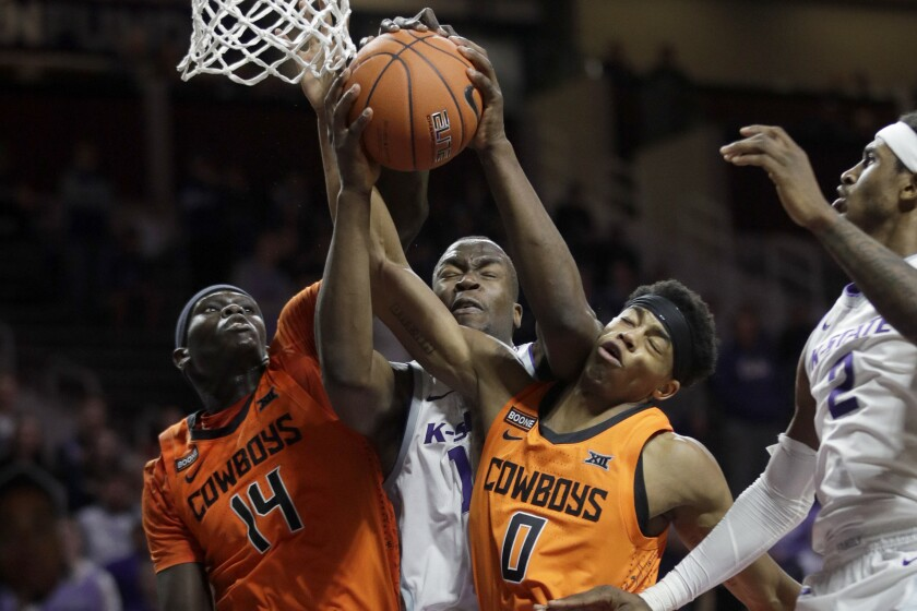 Kansas State forward Makol Mawien, middle, rebounds against Oklahoma State forward Yor Anei (14) and guard Avery Anderson III (0) during the second half of an NCAA college basketball game in Manhattan, Kan., Tuesday, Feb. 11, 2020. Oklahoma State defeated Kansas State 64-59. (AP Photo/Orlin Wagner)