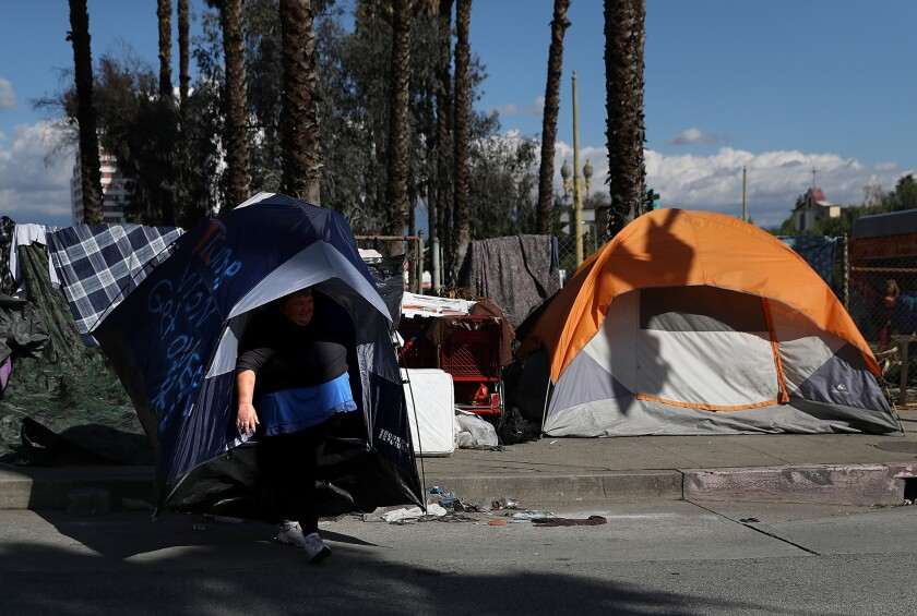 A homeless woman in Los Angeles carries her tent as she relocates her camp in January. County voters will decide on a sales tax measure to reduce homelessness.