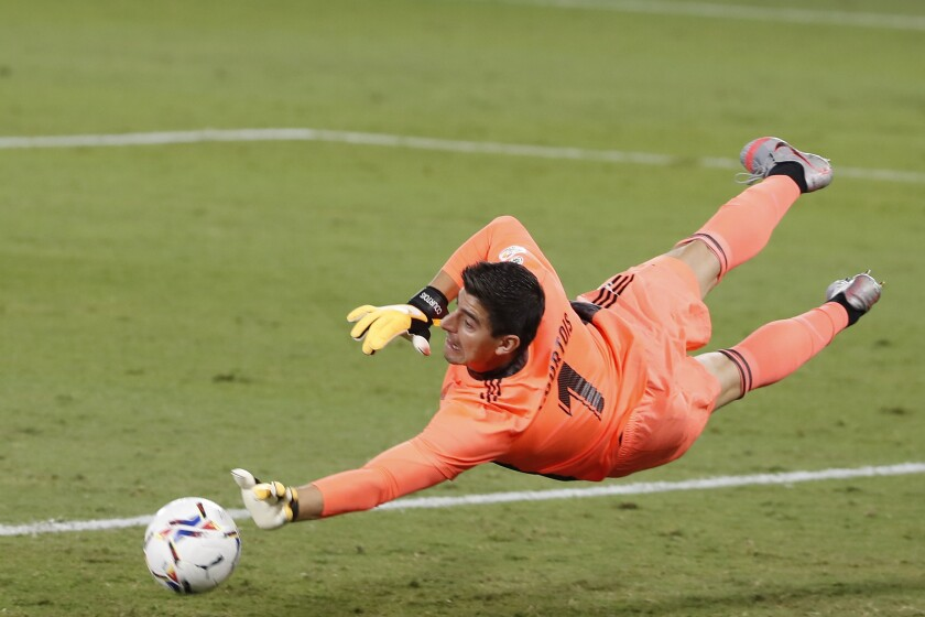 Real Madrid's goalkeeper Thibaut Courtois saves a ball during the Spanish La Liga soccer match between Betis and Real Madrid at the at the Benito Villamarin stadium in Seville, Spain, Saturday, Sept. 26, 2020. (AP Photo/Angel Fernandez)