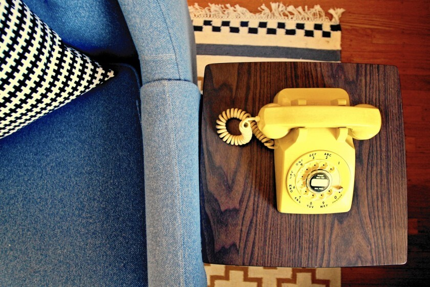 A yellow rotary phone on an end table.