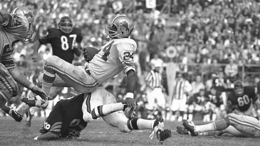 Detroit Lions running back Mel Farr (24) balances atop Chicago Bears back Bennie McRae (26) after sn