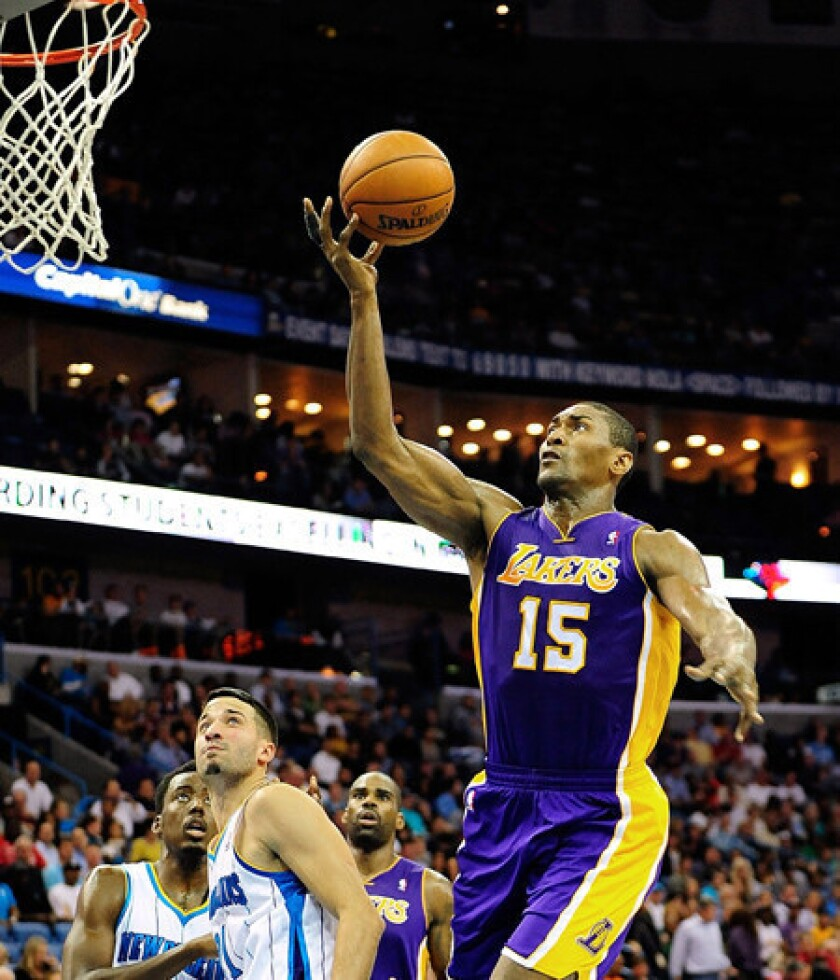 Lakers forward Metta World Peace drives past Hornets guard Greivis Vasquez for a layup Wednesday night in New Orleans.
