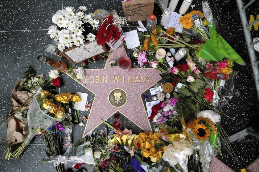 Flowers, cards and candles surround Robin Williams' Hollywood Walk of Fame star. The beloved comedian and actor died a year ago.