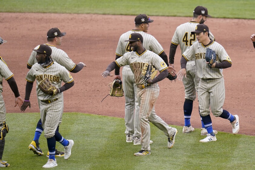 The San Diego Padres greet each other as they leave the field after defeating the Pittsburgh Pirates in a baseball game, Thursday, April 15, 2021, in Pittsburgh. The Padres won 8-3. (AP Photo/Keith Srakocic)