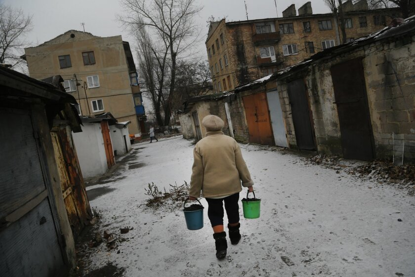 In this Friday, Dec. 6, 2013 photo Lidia Kvakina, 74, carries buckets full of coal to warm her apartment in a town of Ukrainsk, eastern Ukraine. Ukrainsk has just one mine in operation and with about 10,000 residents is half the size it used to be. Many of the Soviet-era apartment buildings are abandoned, their windows broken. Packs of stray dogs roam the streets. (AP Photo/Sergei Grits)
