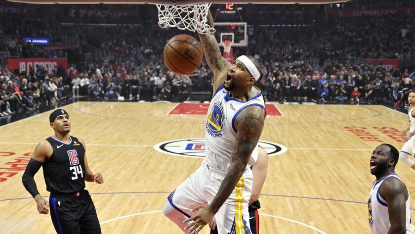 Golden State Warriors center DeMarcus Cousins, center, dunks as Clippers forward Tobias Harris, left, and Warriors forward Draymond Green watch during the first half.