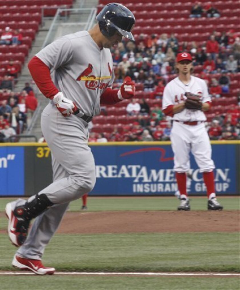 St. Louis Cardianls Carlos Beltran runs to home plate after he hit a home run in the first inning of their baseball game in Cincinnati Tuesday April 10, 2012. Looking on is Cincinnati Reds pitcher Mike Leake who gave up the home run. (AP Photo/Tom Uhlman)