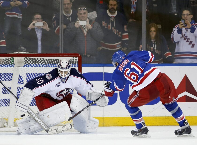 New York Rangers left wing Rick Nash (61) takes his shot in a shootout against Columbus Blue Jackets goalie Curtis McElhinney (30) in overtime in an NHL hockey game at Madison Square Garden in New York, Sunday, Feb. 22, 2015. The Rangers defeated the Blue Jackets 4-3 in a shootout on Nash's goal. (AP Photo/Kathy Willens)