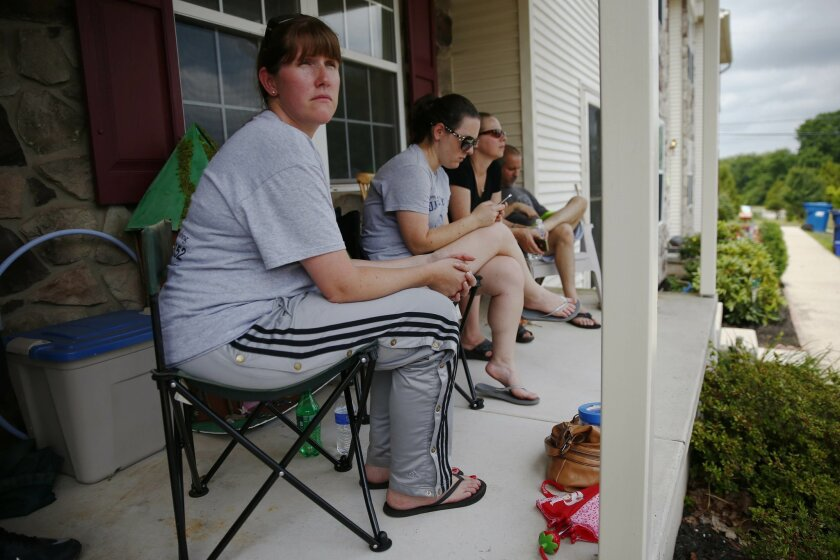 Kourtnay Loughin waits with neighbors for her home to be tested by officials for an odor that begun a voluntary evacuation, Monday, July 14, 2014, in Skippack, Pa. Residents of 150 suburban Philadelphia homes are being allowed to return as their houses are tested after a voluntary evacuation overnight due to a mysterious odor. Officials are awaiting lab results to try to identify the substance responsible for Sunday evening's problem in the neighborhood in Skippack. (AP Photo/Matt Rourke)