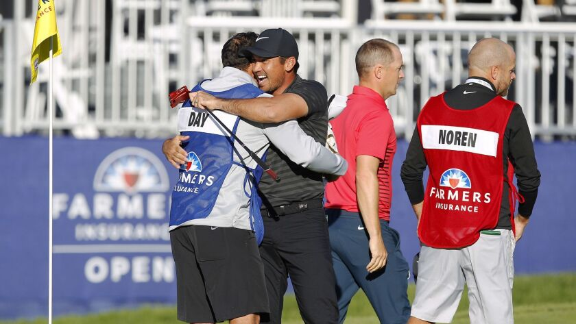 Jason Day celebrates with caddie Rika Batibasaga after winning the Farmers Insurance Open at Torrey Pines Golf Course on January 29, 2018. Day beat Alex Noren, right, in a playoff.