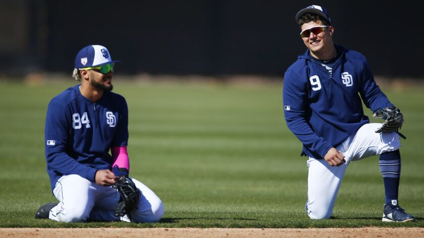 San Diego Padres infielders Fernando Tatis Jr., left, and Luis Urias wait for drills during a spring training practice on Feb. 20, 2019.