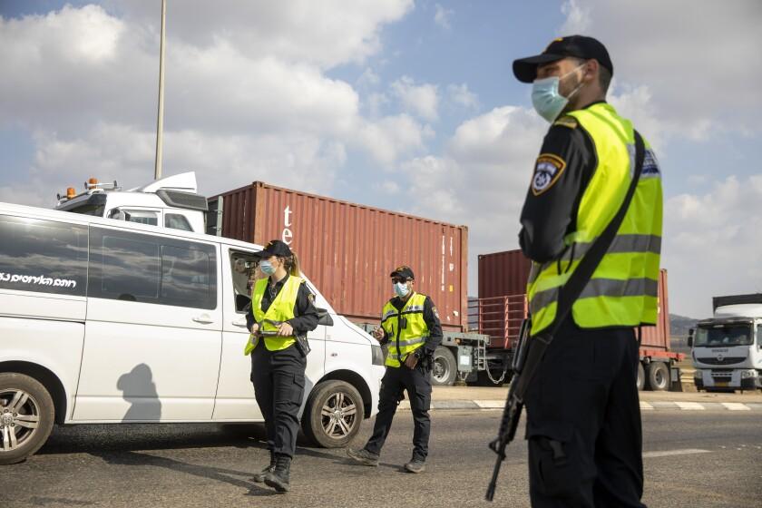 Three people in uniform watch a van.