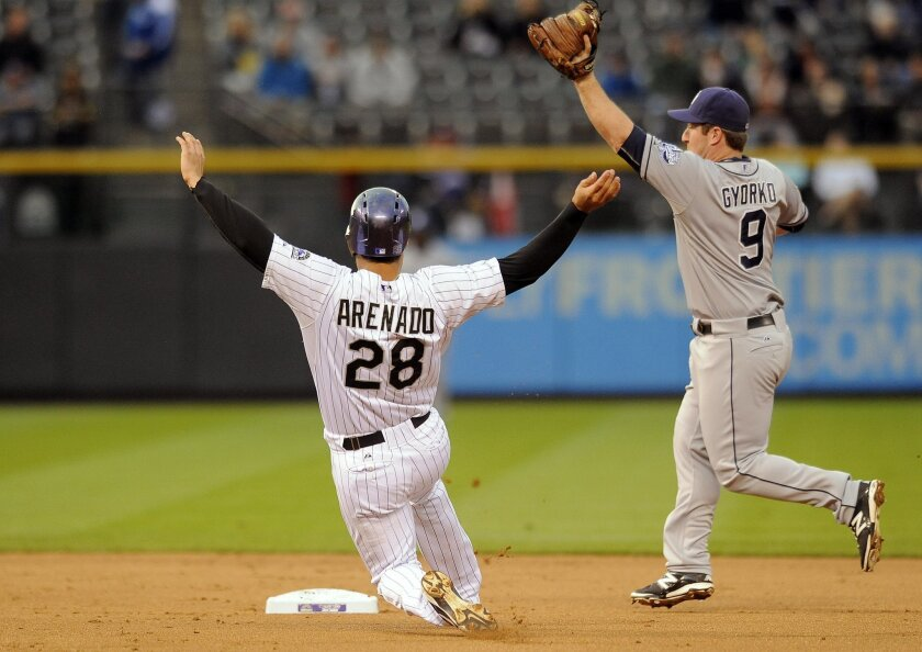 Colorado Rockie' Nolan Arenado is forced out at second base by San Diego Padres second baseman Jedd Gyorko in the first inning of a baseball game Friday, Sept. 5, 2014, in Denver. (AP Photo/Chris Schneider)