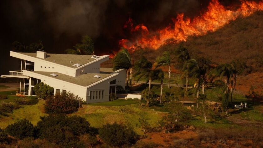 A line of fire approaches a home east of Lake Ramona during the 2007 wildfires that scorched San Diego County.