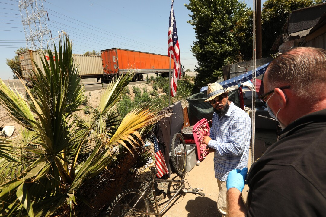 Outreach worker John Oliver, right, talks with Carlos Aguirre, who lives in an encampment along the 710 Freeway.