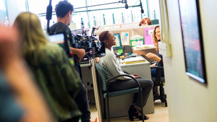 Actress Issa Rae, seated at left, between scenes, with actress Lisa Joyce on the set of HBO's second