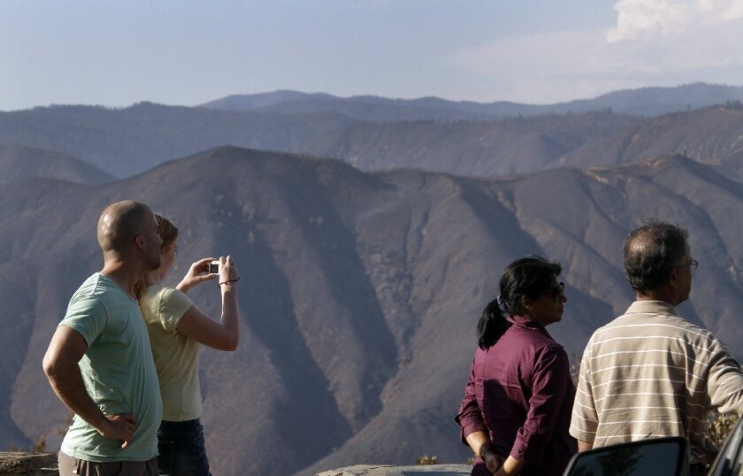 Tourists at the Rim of the World vista point near Yosemite look at the burn area Friday.