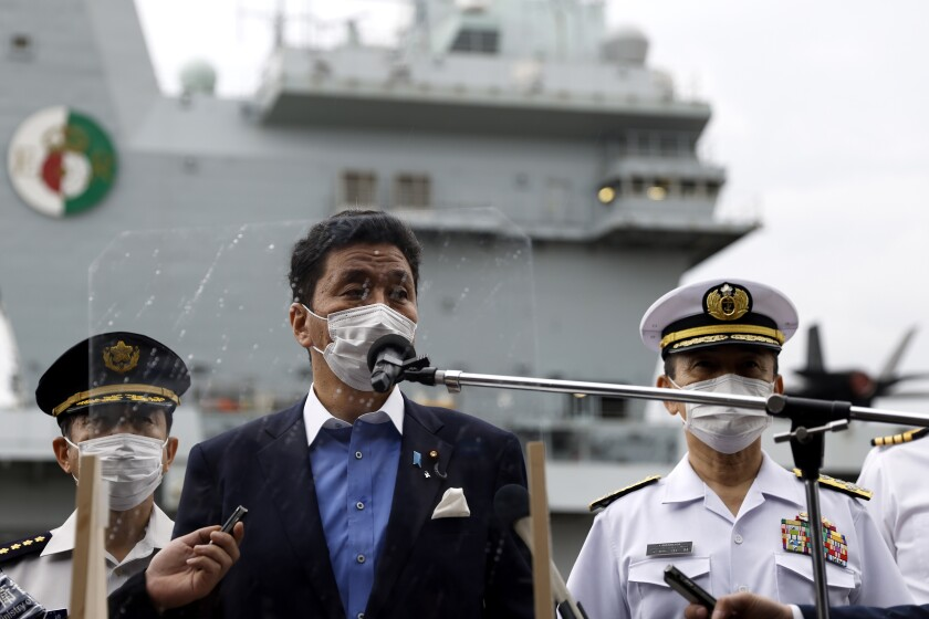 Japan Defense Minister Nobuo Kishi speaks to the members of the media after he inspected the British Royal Navy's HMS Queen Elizabeth aircraft carrier, back, at the U.S. naval base in Yokosuka, Kanagawa Prefecture, Japan Monday, Sept. 6, 2021. (Kiyoshi Ota/Pool Photo via AP)