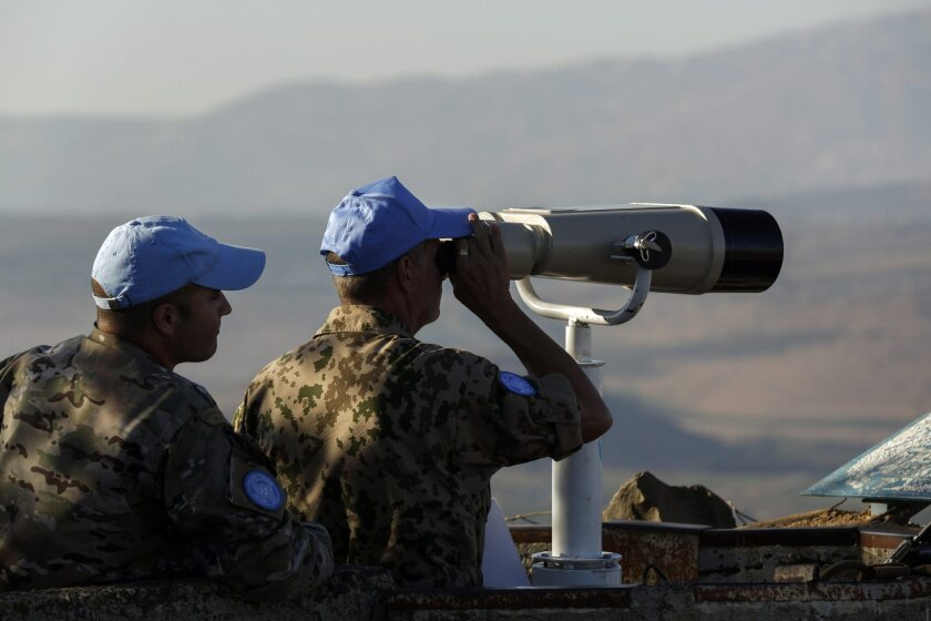 U.N. soldiers watch the Israeli-Syrian border from the Golan Heights on Aug. 21.