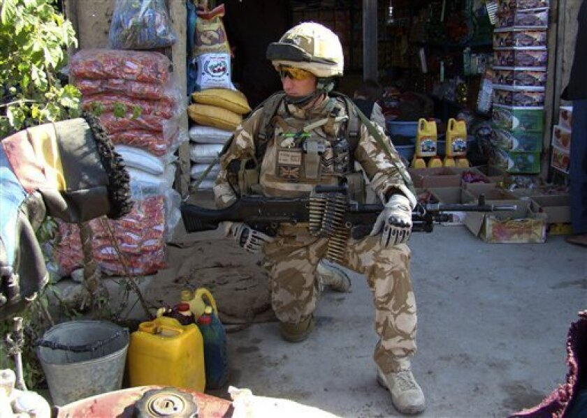 A British soldier with the NATO led- International Security Assistance Force (ISAF) knees down on the ground while patrolling in Sangin district of Helmand province, south of Kabul, Afghanistan, Wednesday, Dec. 2, 2009. (AP Photo/Abdul Khaleq)
