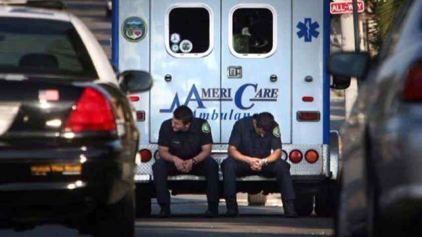 LOS ANGELES, CA – JULY 30, 2011: Ambulance crew sits on the back of their AmeriaCare Ambulance on Br