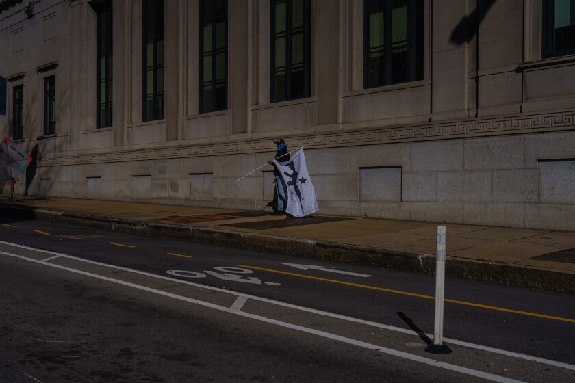 A person walks with a flag in Richmond, Va., on Monday.