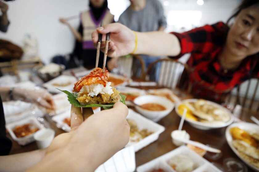 Students taste the completed kimchi atop steamed pork after Jessie Kim's cooking class in November.