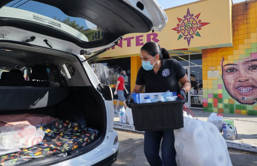 Nancy Maldonado, CEO of the Chicano Federation of San Diego County, places cleaning supplies and a sanitation kit in the vehicle of an essential worker in front of the Federation's Barrio Logan Child Development Center.