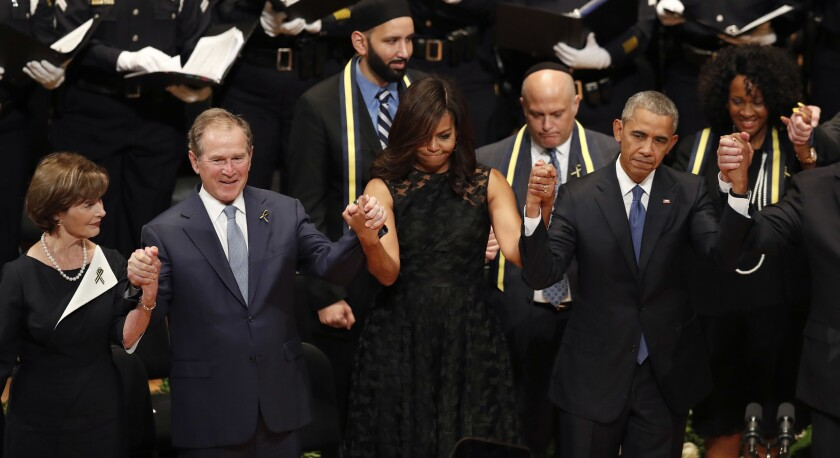 De izquierda a derecha, la ex primera dama Laura Bush, el ex mandatario George W. Bush, la primera dama Michelle Obama y el presidente Barack Obama se toman de las manos durante la ceremonia funeraria de los cinco policías que murieron a tiros en Dallas la semana pasada, el martes 12 de julio de 2016, en Dallas. (AP Foto/Eric Gay)