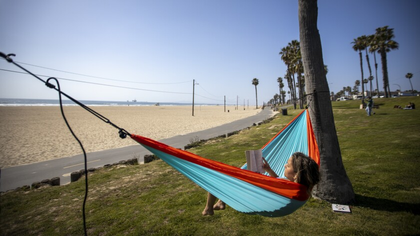 Kylie Wortham, who was laid off when her company closed due to the pandemic, relaxes in a hammock in Huntington Beach.