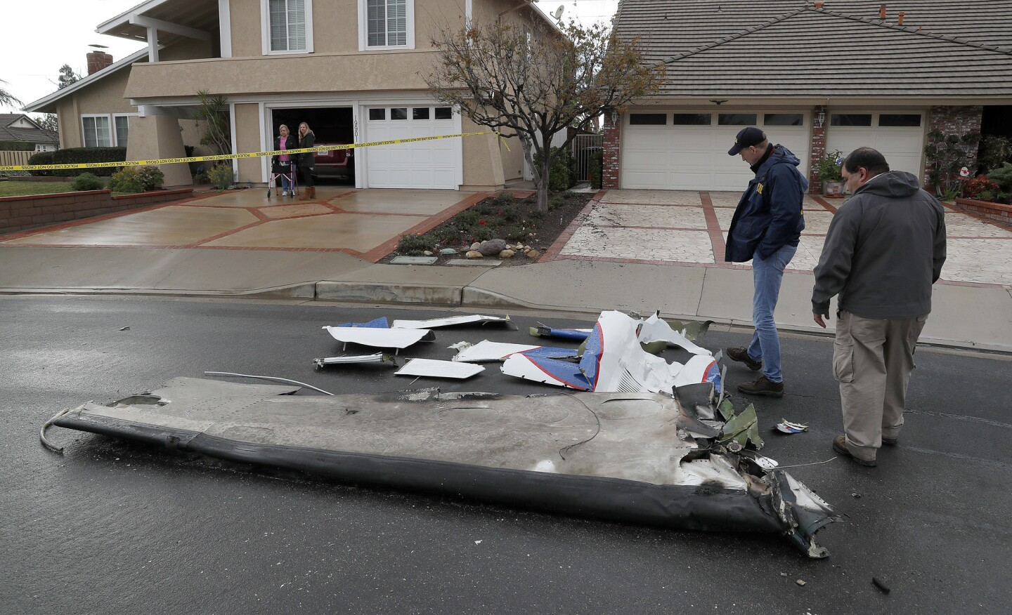 Peter Knudson, a media relations specialist with the National Transportation Safety Board, left, and air safety investigator Ricardo Asensio review pieces of a Cessna airplane that crashed into a Yorba Linda home. Five people, including pilot Antonio Pastini, were killed.