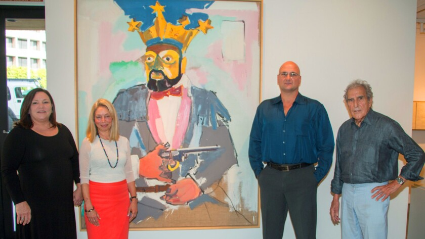 At the Aug. 31 reception, José Tasende (far right) poses with his daughter Betina (far left), gallery director Mary Beth Petersen, and his son Aitor. Behind them is 'American Crown,' a painting by German artist Lambert Maria Wintersberger.
