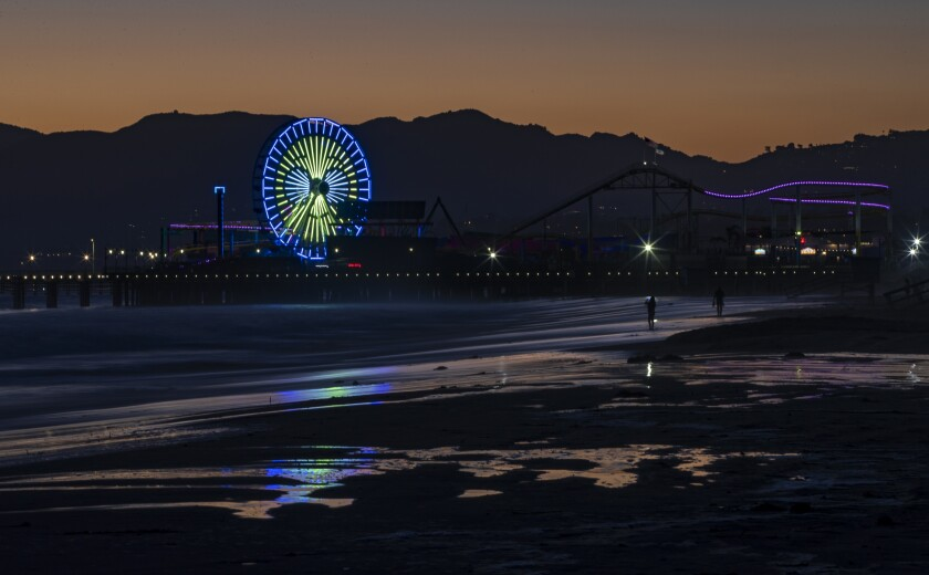 The Ferris wheel begins to change to patriotic colors at dusk on the Santa Monica Pier for the July 4 holiday weekend.