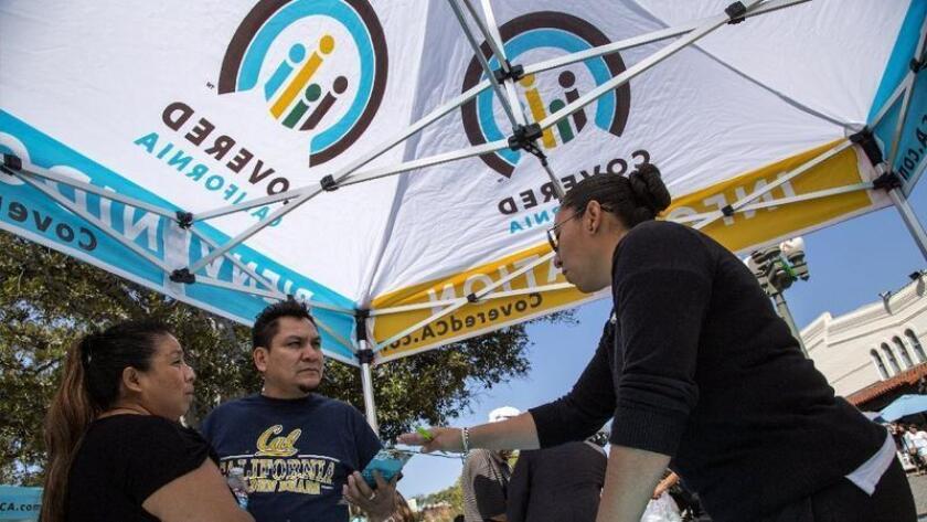 Ana Oliva, de lado izquierdo, y Félix Portillo de Los Angeles reciben más información sobre la inscripción a Covered California por parte de Valeria López en un evento de marzo del 2014.