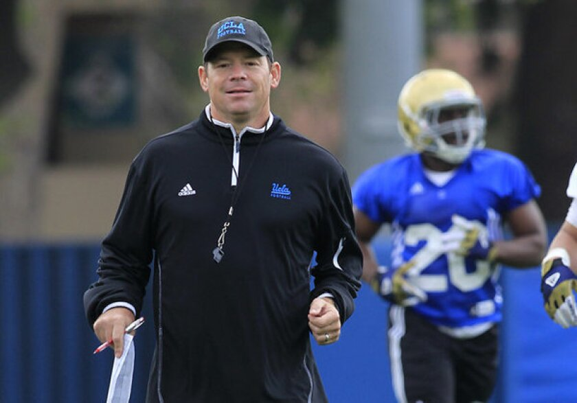 Coach Jim Mora watches practice on the field at UCLA.