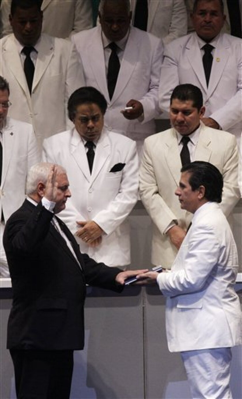 Panama's President-elect Ricardo Martinelli, left, is sworn in as new president by Jose Luis Varela, president of the National Congress, during a ceremony in Panama City, Wednesday, July 1, 2009. (AP Photo/Arnulfo Franco)
