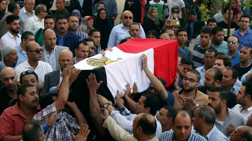 People carry the coffin, covered with the an Egyptian flag, of police captain Ahmed Fayez who was ki
