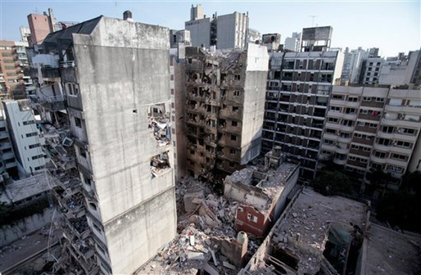 This view shows two other towers, in front of and behind a 10-story apartment building destroyed by a Tuesday gas explosion that killed 10 people, in Rosario, Argentina, Wednesday, Aug. 7, 2013. Argentine firefighters found signs of life Wednesday, searching through a huge pile of rubble, all that was left of a 10-story apartment building destroyed by a gas explosion that injured dozens and left 13 unaccounted for. (AP Photo/Alejandro Rio)