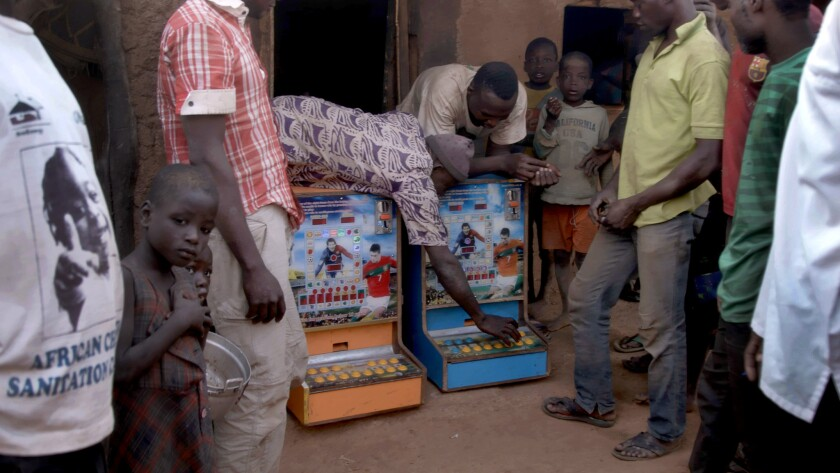 Villagers bring two gambling machines out from a hut in Zamashegu, Ghana.