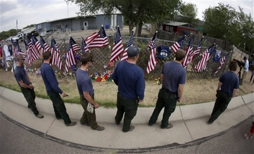 Members of the Centennial Initial Attack Fire Crew, from Island Park, Idaho, pay their respects at a memorial outside the Granite Mountain Interagency Hotshot Crew fire station, Thursday, July 4, 2013, in Prescott, Ariz. Nineteen firefighters from Granite Mountain Interagency Hotshot Crew were killed battling a wildfire near Yarnell, Ariz., Sunday. The elite crew of firefighters were overtaken by the out-of-control blaze as they tried to protect themselves from the flames under fire-resistant sh
