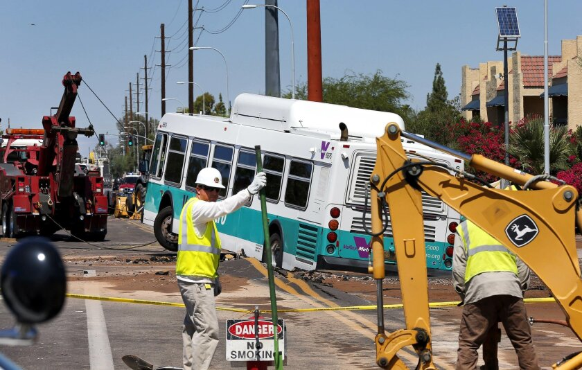 A valley metro bus sits mired in a collapsed, muddy street after a water main break flooded the area, Wednesday, Sept. 3, 2014 in Tempe, Ariz. Police say police officers and firefighters helped passengers get off the bus and that nobody was injured during the Wednesday morning incident though some businesses were flooded. (AP Photo/Matt York)