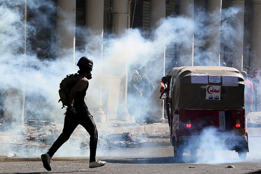 Iraqi riot police fire tear gas to disperse anti-government protesters in Baghdad on Friday.
